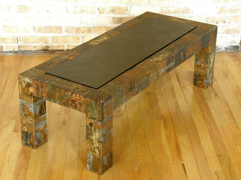 Studio made coffee table with patchwork copper and brass clad surface. The metal pieces are patinated and enameled with applied, torch cut, and ground down textures in the finish. The nailheads that attach the various pieces are a tactile and