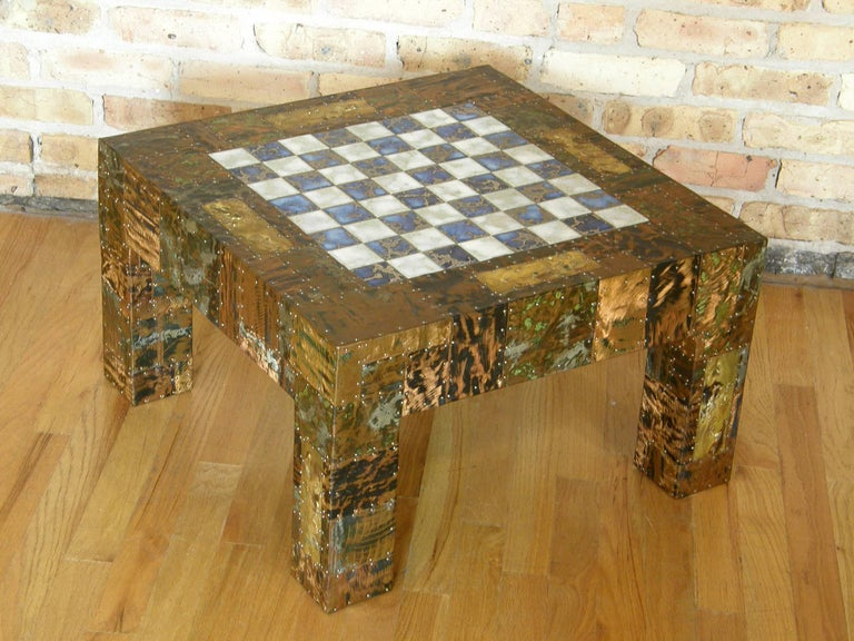 Studio made game or chess table with patchwork copper and brass clad surface. The metal pieces are patinated and enameled with applied, torch cut, and ground down textures in the finish. The nailheads that attach the various pieces are a tactile and