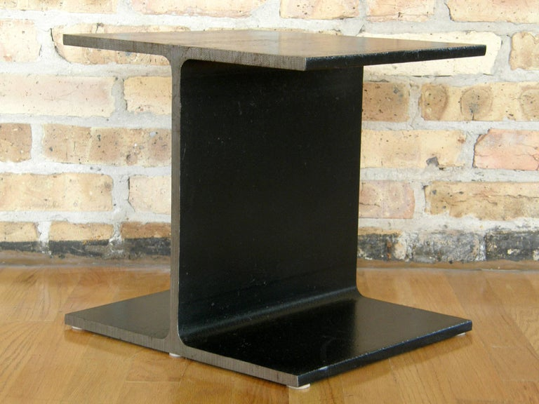 Minimalist side table in the form of a slice of an I-beam. The Classic Industrial form of the I-beam has been domesticated by removing it from it's context and bringing it to an intimate scale. The flat surfaces have a black enameled finish, and the