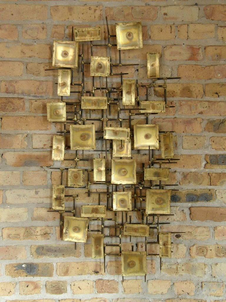 "Three dimensional, brutalist wall sculpture with a frame of square nails set with torch cut and patinated brass rectangles. Signed ""Charles '74"".