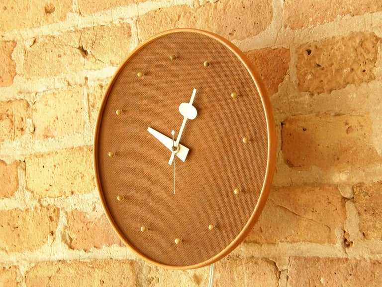 Electric wall clock designed circa 1950 by George Nelson Associates for Howard Miller with a masonite face, numbers resembling push pins, and a birch frame.