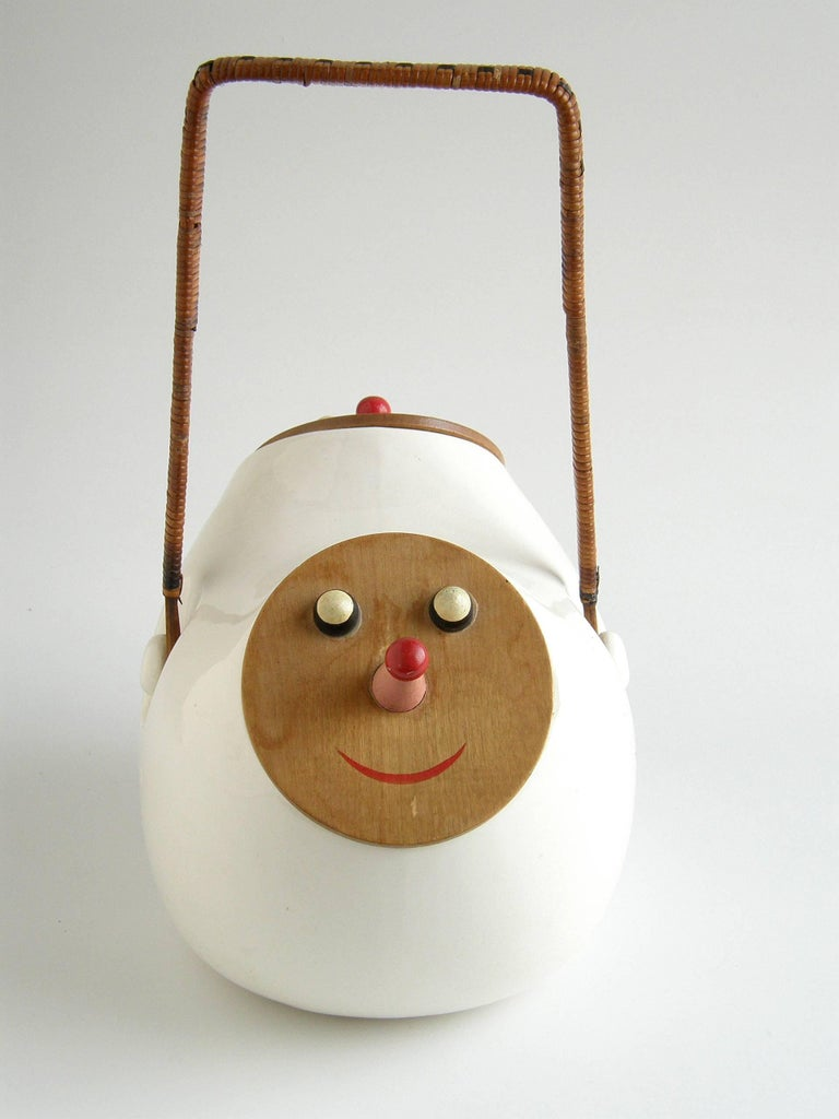 This amusing ceramic cookie jar designed by Lagardo Tackett has an opening on each side. The lids of the two openings are made of wood and painted with clownish, smiling faces. Their red-tipped pink noses form their handles. The tall, woven rattan