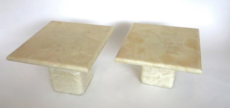 """A pair of side tables on square pedestals in cream ivory colored cultured marble.  They can be used as paired coffee tables or side tables.  No chips or restorations. Taller: 21"""" x 21"""" x 15.5"""". Shorter: 21"""" x 21"""" x 12"""". Plateau 1.5"""" thick."""