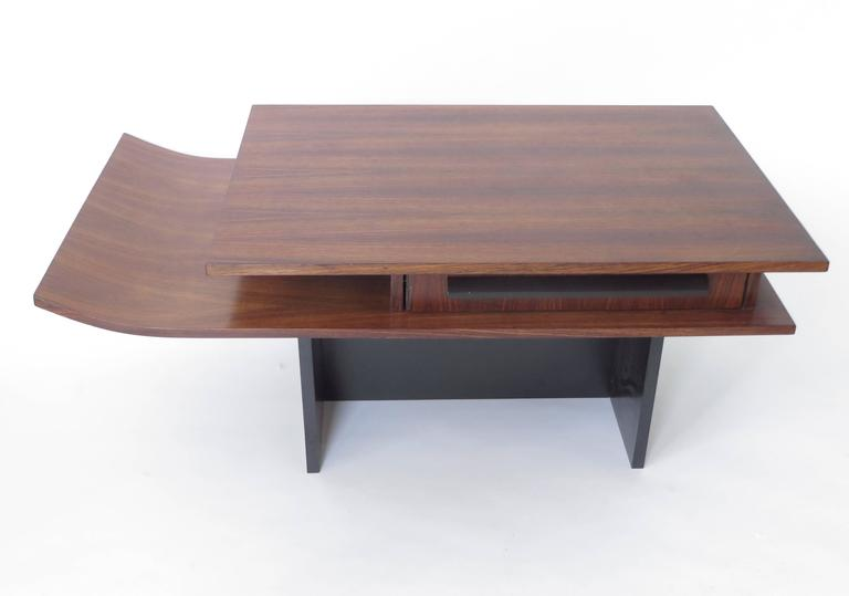 An coffee table of unknown designer made of two levels of rosewood, one level with a gently sloping upward curve. One drawer with ebonized rosewood drawer pull sitting on black laminate base. 