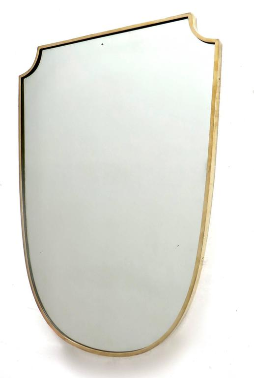 A shield shaped Italian brass framed mirror with beautiful patina and no flaws to the original mirror, circa 1940.