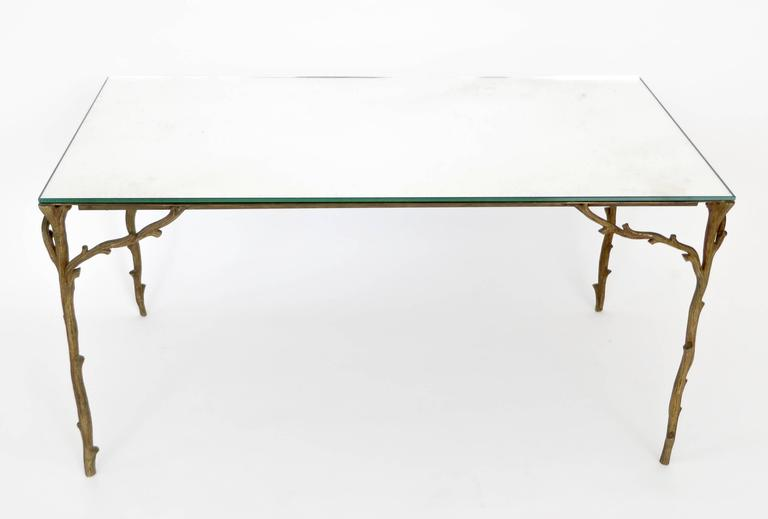 This Maison Bagues bronze based coffee table with very animated bronze legs of branches and not the typical faux bamboo makes it more rare.  The vegetal and wood shaped design ornament is very organic and lyrical. The top is a mirrored glass with a