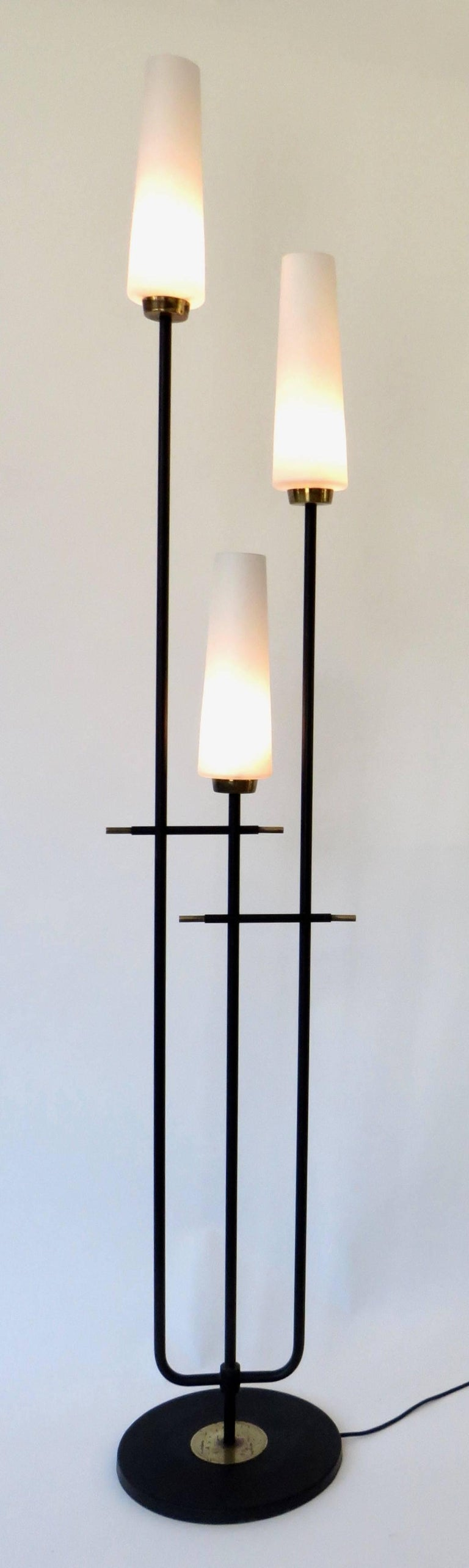 French floor lamp by Maison Lunel, black iron with brass accents, and three cased, blown glass shades. Rewired for USA. Takes candelabra base bulbs, 60w maximum.
