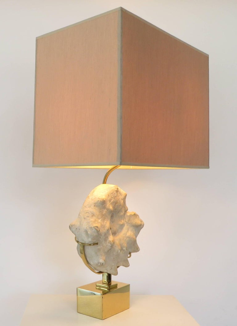 A mounted ammonite Belgian specimen lamp with taupe silk shade on a brass base in the style of Willy Daro, circa 1970s.