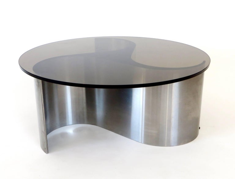 A coffee or side table model Comete designed by Patrice Maffei and produced by Uginox/Kappa, France, circa 1970. The curving stainless steel wave form of this low coffee table was often used in a taller dining table as well.  This has a beautiful