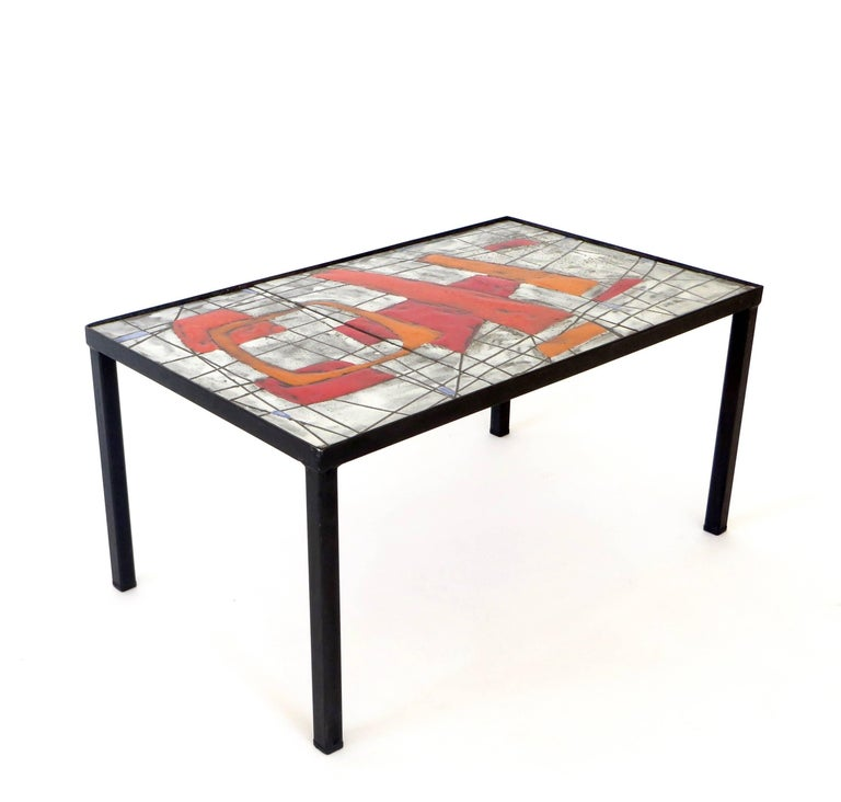 A boldly colorful and graphic ceramic tile glazed top with black metal leg structure, circa 1960, France. Colors of orange, red, grey, black and touches of blue by Jean and Robert Cloutier. 