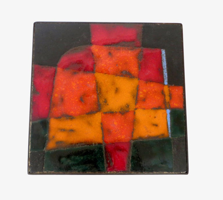 A boldly colorful and graphic ceramic tile glazed top with black metal leg structure, circa 1960, France. Colors of orange, red, black and touches of blue by Jean and Robert Cloutier.   