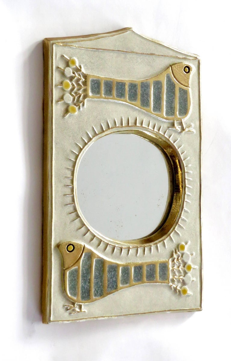 A French ceramic mirror by Francois Lembo with stylized bird motif and sun motif.