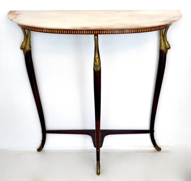 Italian neoclassical Art Deco demilune console attributed to Paolo Buffa with a cream peach Brescia Primavera marble top. The apron has a finely done inlay.  There are carved gilded swan supports at the top of the hand-carved mahogany legs