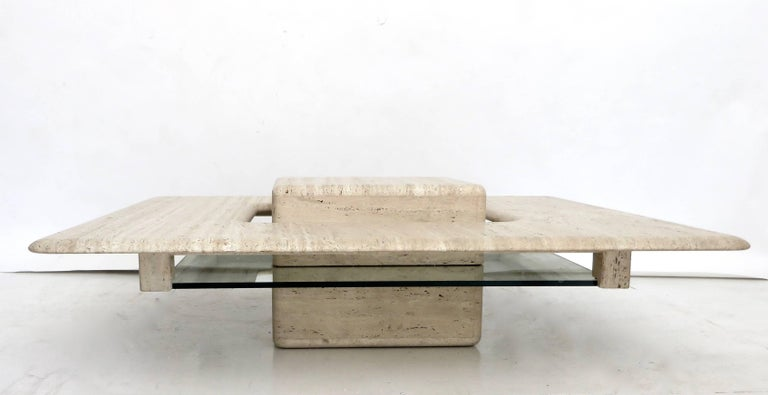A Minimalist French circa 1970 travertine marble coffee table. Italian honed matte and natural travertine marble low square coffee table with a floating cube in the centre that is elevated by a piece of glass that is semi noticeable. The cube then