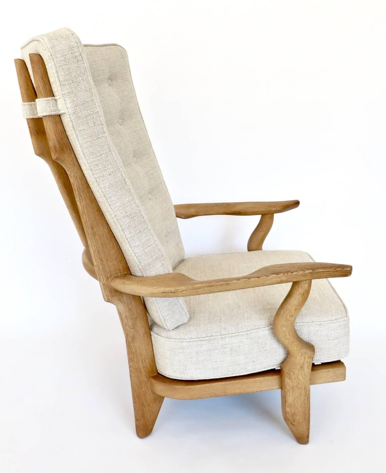Two extraordinary French Guillerme and Chambron high back lounge chairs in solid oak with the typical characteristic long finger motif at the backs for Votre Maison. The