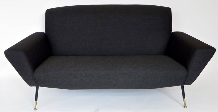 """A circa 1950 midcentury Italian settee or small sofa with black and brass legs totally re upholstered in a charcoal holly hunt linen wool blend. The seat itself without the arms is 49"""" W x 20"""" D x 33"""" H. The total width is 66""""."""