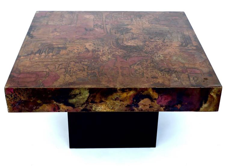 A large etched abstract scene Belgian signed coffee table on a black wood base.  The undulating abstract design in copper and brass and varying shades of darkened copper, black and red patina, with raised areas.  Smooth patinated copper sides,