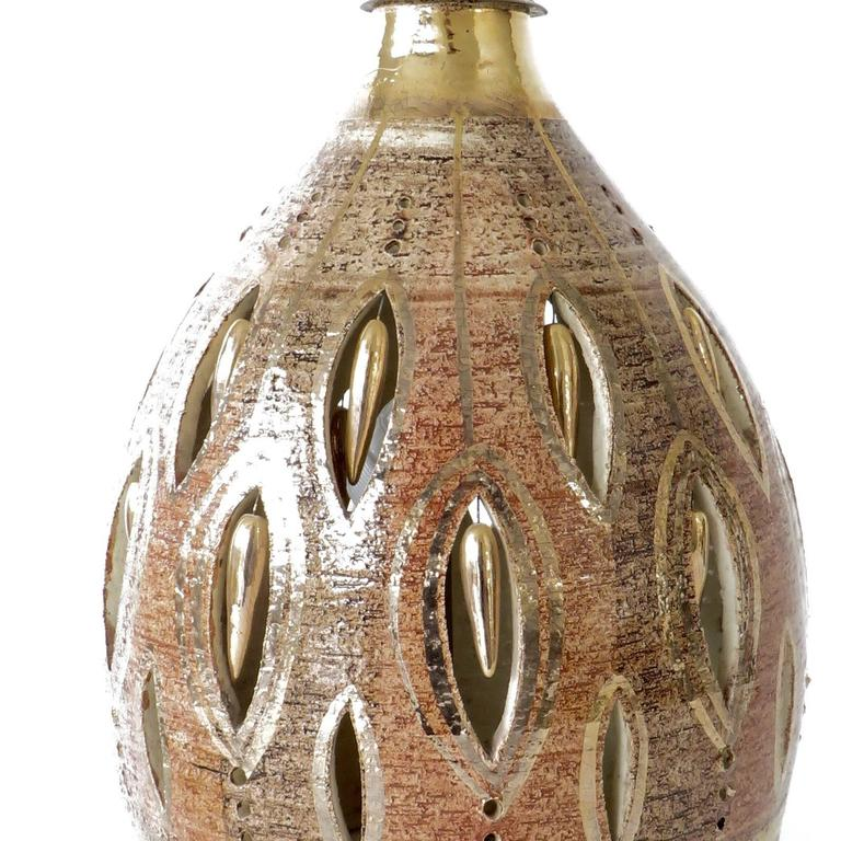 A large French ceramic table lamp by the French artist Georges Pelletier. Beautiful varying shades of brown, rust and gold lustre glaze and gold pastilles and incised abstract cutouts on a heavily grogged body gold lustre detailed glazed body.