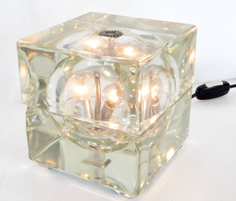 """The """"Cubosferea"""" table lamp by Alesendro Mendini, editioned by Fidenza Vetraria, circa 1960s. Cast glass, hollow cube, that houses two light sockets. As shown, unfortunately there is a chip off one corner of the bottom that portion of the light,"""
