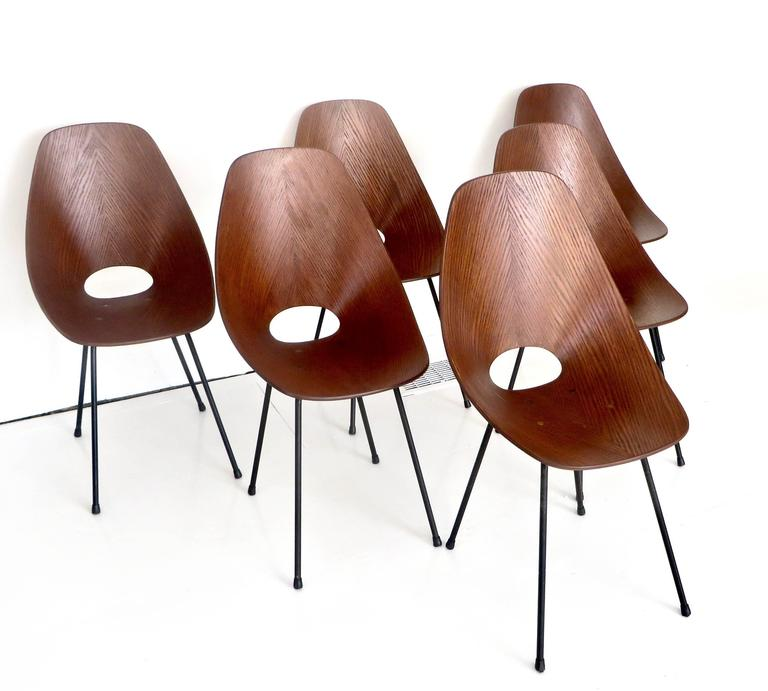 """Six famous """"Medea"""" dining chairs designed by Vittorio Nobili for Fratelli Tagliabue. Medea chairs, designed in 1955 and winner of the Compasso D'oro in the following year. Moulded teak with black enameled metal structure and legs, with"""