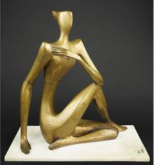 Patinated bronze sculpture of a seated cross-legged woman.
