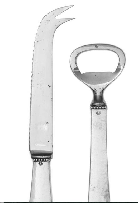 A Danish silver bar set of Georg Jensen Silversmithy, Copenhagen. In the beaded pattern, comprising a bottle opener and bar knife. Marked on handles. Length of bar knife 7 1/4 inches.