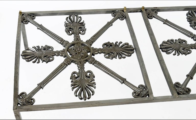 An Iron Cocktail Table Made Of Architectural  Elements. Patinated iron table with non figural decoration and raised on four straight legs 18