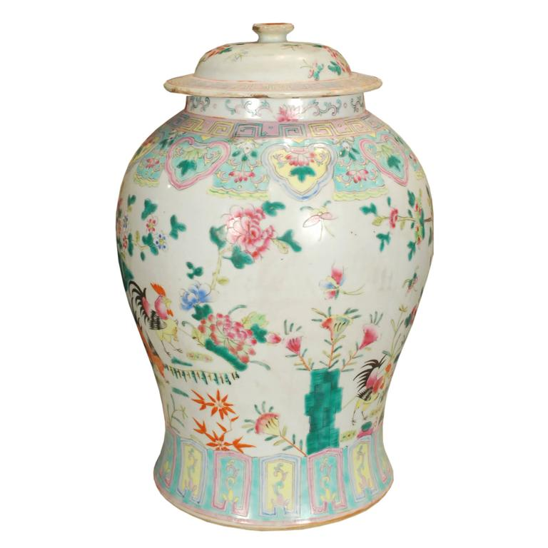 This overglazed porcelain jar from Southern China was painted by hand at the turn of the century with roosters in a flowering garden, representing the charms of rural life. This intricate and colorful style of porcelain gained popularity in the 19th