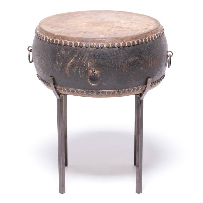 This late 19th-early 20th century wooden drum was made by hand in Beijing, China. The hide top and bottom is finished with handmade iron nailheads. This drum would have originally been used in a procession or possibly as part of a Peking opera