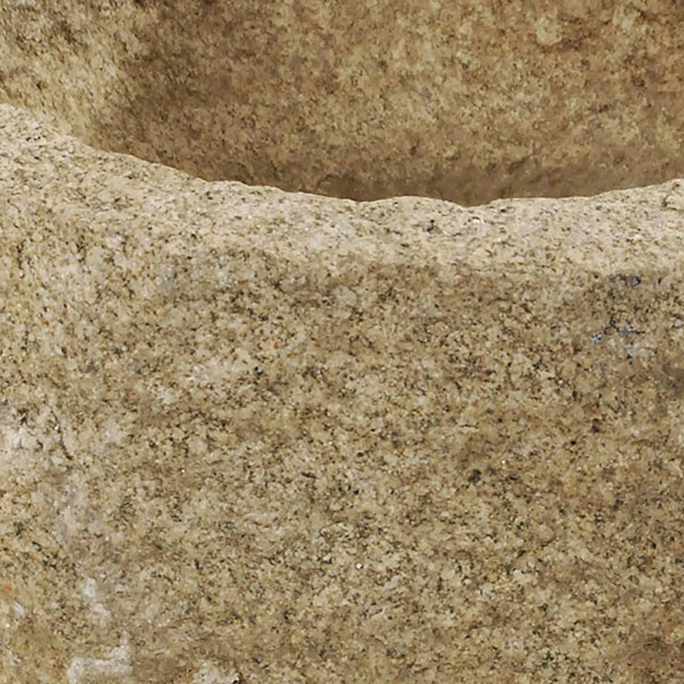 This organically shaped 19th century vessel was carved by hand from a single block of granite. It was originally used in Northern China as a grain mortar. The recess is relatively shallow, making it ideal today as a planter or a simple and