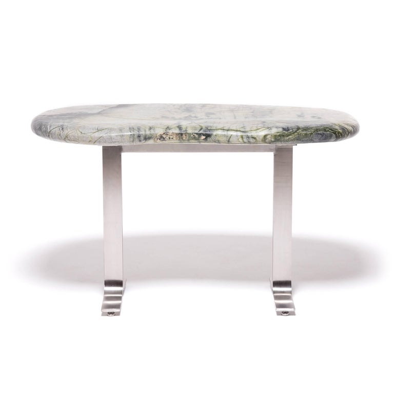 Prized by ancient scholars, meditation stones invigorated the imaginations of poets, painters, and calligraphers. The abstract shape and veining of the greenery stone specimen that tops this table is composed of jadeite, moss agate, serpentine, and