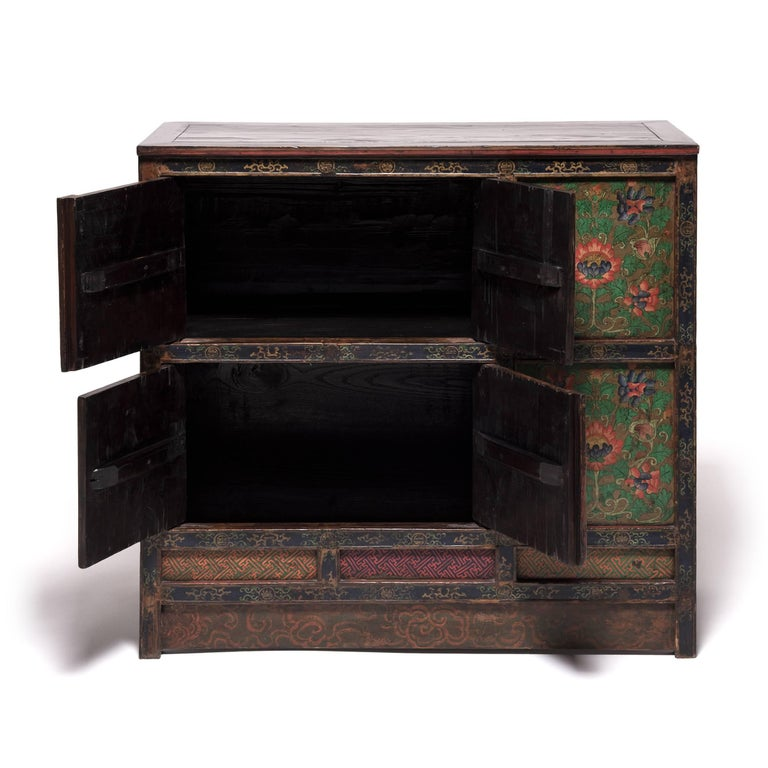 Made in 19th century Tibet, this extraordinary cabinet is lavishly decorated from end to end with beautifully painted floral motifs. Paneled doors depict a repeated motif of intricate, stylized lotuses, still vividly colored after a century of use.