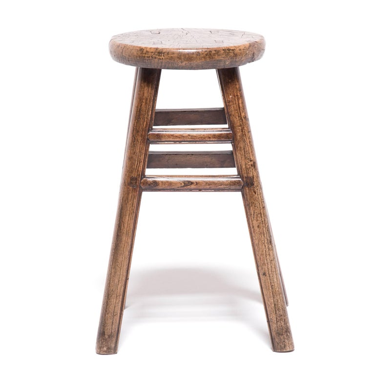 Like the full moon displaying its craters and ridges, the round seat of this otherwise straightforward stool displays the swirling grain and unusual markings of burled wood. Cultivated from irregular growths on trees, this type of wood is prized for