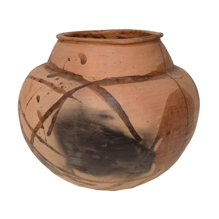 Rustically shaped, this terracotta vase looks like an ethnographic find. The decoration is sparse and gestural, including dashed and splattered strokes, broad translucent patches and smudged sections. Beautifully modern and archaic at the same time,