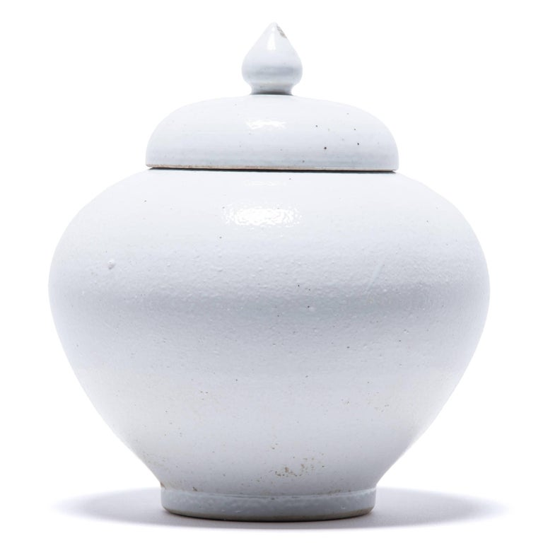 Made in Jiangxi province in 2015, this stunning lidded jar reinterprets traditional Chinese ceramic design with simplified lines. A clean, white glaze calls attention to the jar's undulating curves.