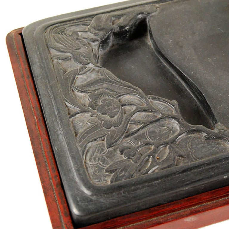 This 19th century inkstone is designed with a water well that follows the shape of the auspicious birds and flowers that define it. The stone fits like a glove into its wooden case. This stone was used at the time when Chinese scholars would retreat
