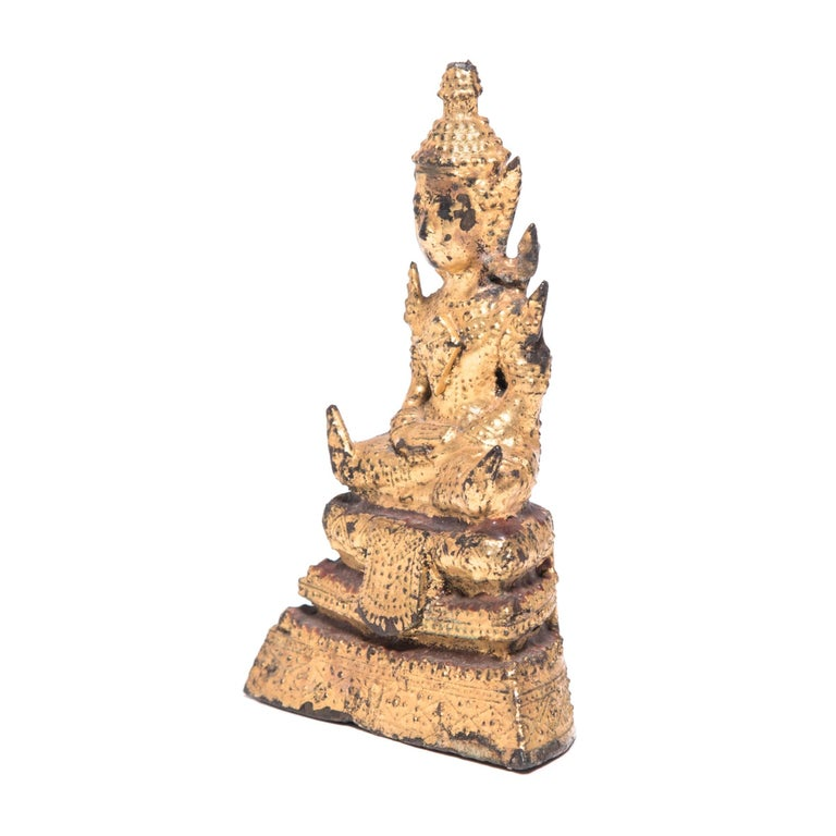 This petite Thai Buddha is a gallery favorite. With legs crossed and his hands in a meditative gesture known as a mudra, the Buddha is depicted in a transcendental state of meditation. Currently displayed inside a lovely rootform shrine, the eye