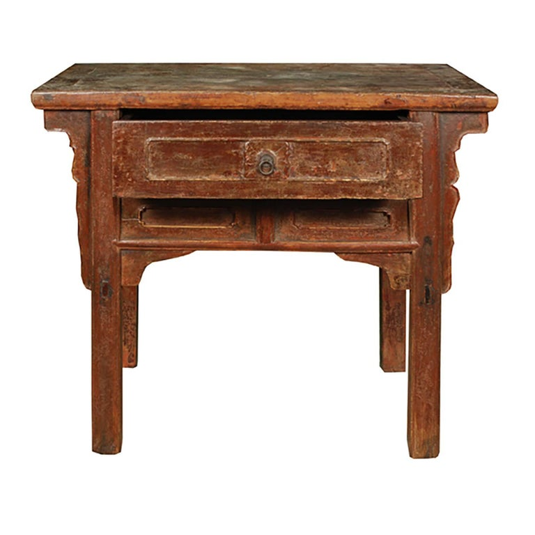 Crafted of Chinese elmwood with the original lacquer still visible, this 19th century provincial table chest mixes simple forms with subtle ornamentation. Featuring a plank top and a single drawer with brass hardware, the chest has a rustic feel