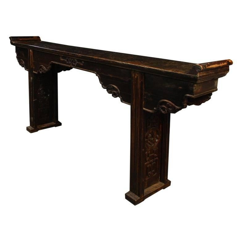 "Slender, long tables like this are often referred to as ""altar tables."" In ancient China they were used to hold musical instruments or display items of beauty and wealth such as jade, arrangements of flowers, or porcelain vases. This elegant elmwood"
