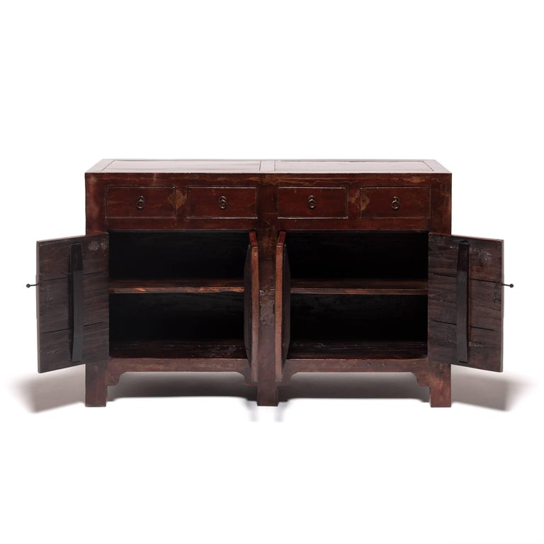 This 19th century coffer created in Northern China started its life as a storage trunk with a solid lacquered front. Artisans skilled in traditional Chinese carpentry reconfigured it into a four-door chest with four drawers, brushing by hand