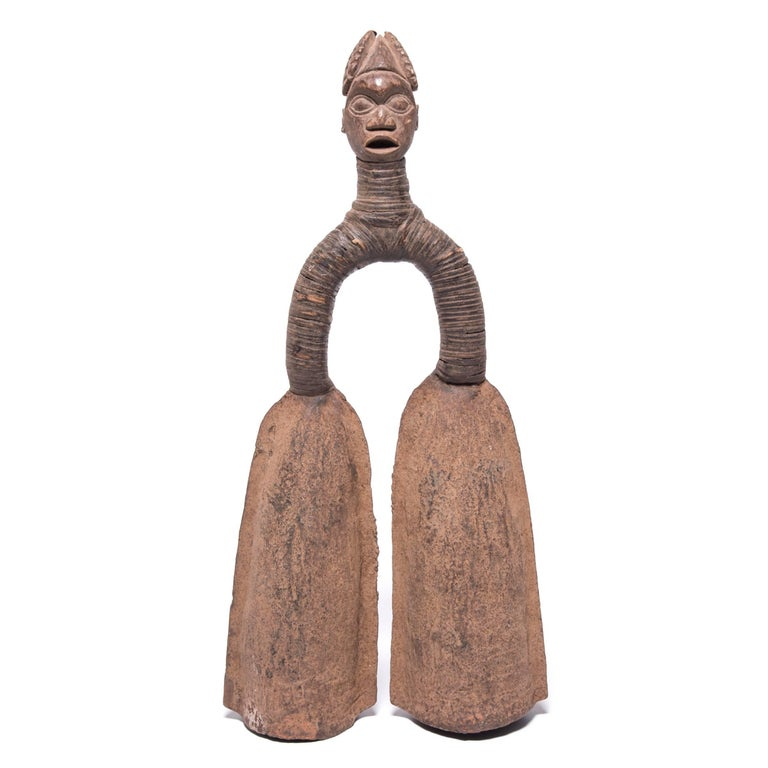 Like many pieces of traditional African metalwork, this pair of sculptural double bells served multiple purposes for the tribe. They were ceremonial instruments, status symbols, and traded as currency. Using a rubber coated stick, members of the