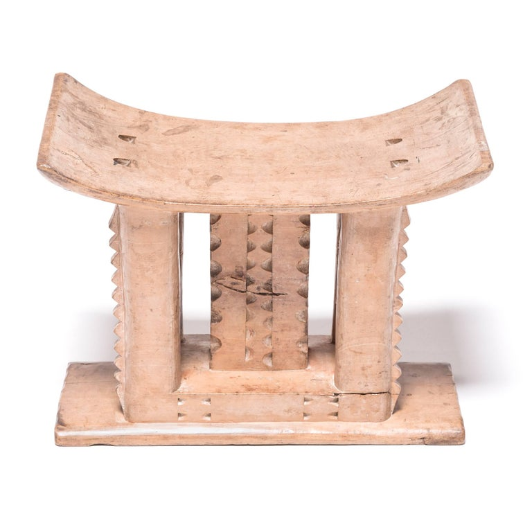Stools indicated power, status, and lines of succession in traditional Ashanti culture. The flat base, curved seat, and ridged supports reference the Ashanti King stool. While many stools of this type incorporate carvings from the Adinkra symbol