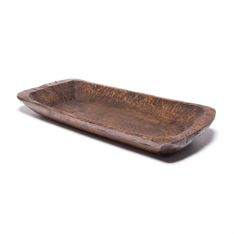 Carved from a single piece of northern Elmwood, this hundred year old butcher's tray made in Shanxi province charms with its rusticity and organic form. Marked with use and distinguished by the natural grain and knots of wood, the rectangular tray