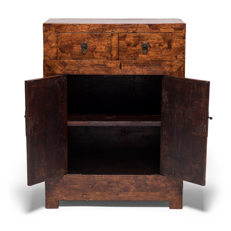 A rare find in Chinese furniture, the entire front of this unusual early 20th century cabinet is covered in parquetry veneer, a complex, decorative carpentry technique of matching precision-cut blocks of inlaid wood. The top and bottom portions of