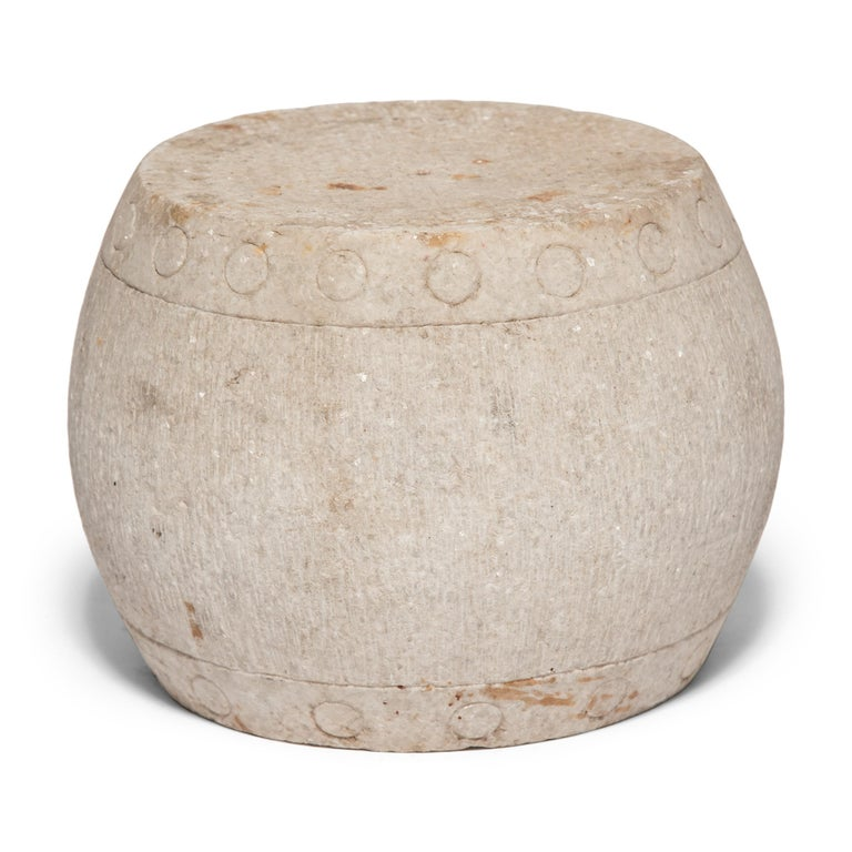 This drum form pedestal was carved from a single block of white marble by Qing-dynasty artisans in the mid-19th century. Ringing both its top and bottom, an etched pattern of nail heads imitates those used to stretch a skin on an actual drum. At the