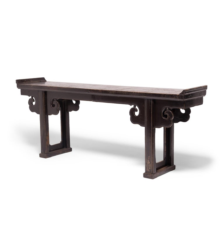 Created in China's Shanxi province in the early 19th century, this impressive altar table with everted ends features straight legs joined with a base stretcher, topped by hand-carved spandrels resembling billowing clouds. Constructed with