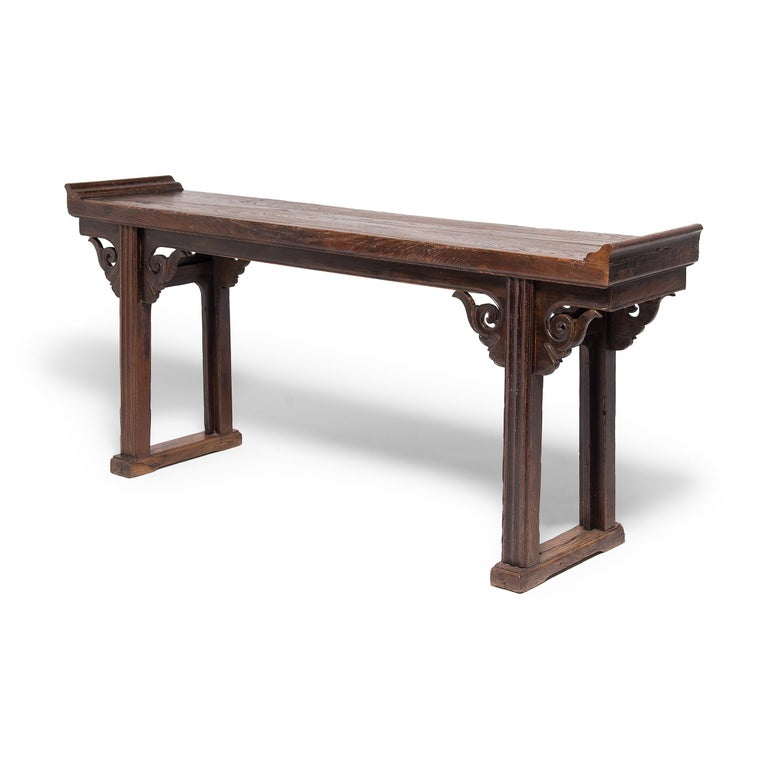 With everted ends and square legs, this altar table expresses Classic Qing-dynasty design, but the hand-carved spandrels are extraordinary and truly set the design apart. Trimmed with a finely beaded edge, the spandrels are carved with a scrolled