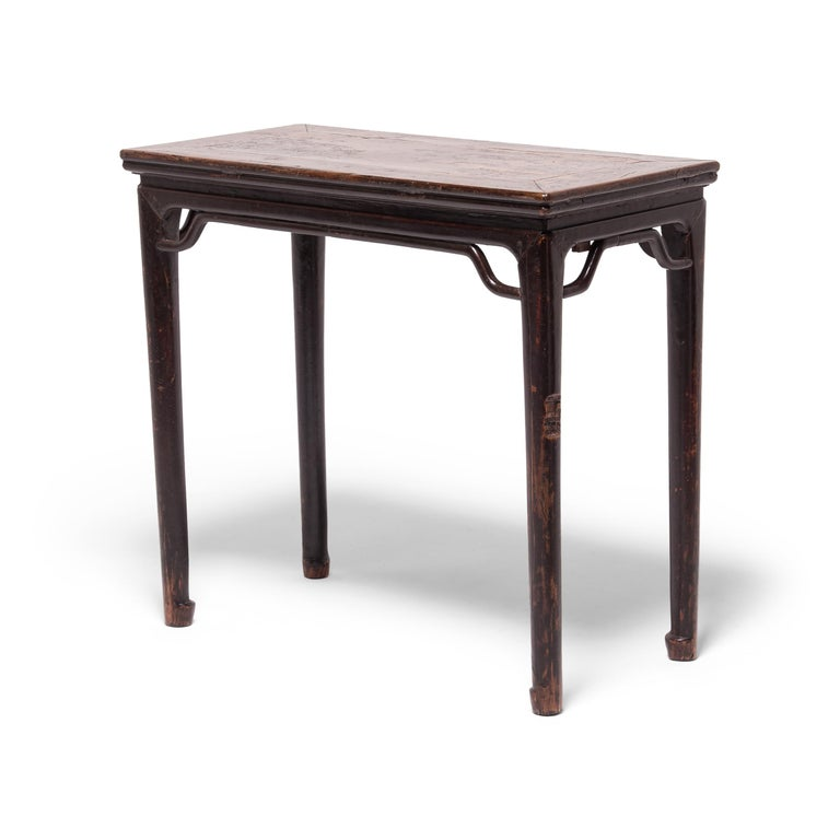 Crafted of dark brown walnut, a wood prized for its open-grained texture and warm tones, this 19th-century wine table expresses the refined forms of Ming-dynasty furniture. With clean lines and a dark lacquer finish, the table's streamlined form