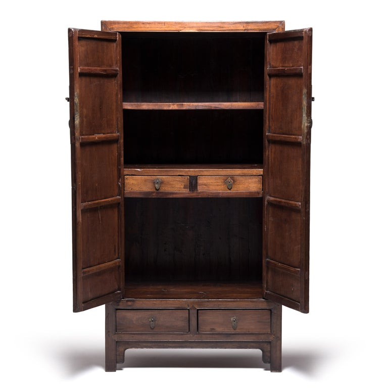 Although elaborate decoration became increasingly common in Qing-dynasty furniture design, the Ming-dynasty's legacy of clean, elegant lines remained a powerful influence as seen in this statuesque scholar's cabinet. Made of warm-colored cedar, the