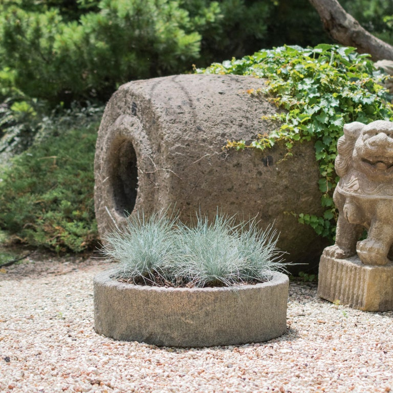 This millstone was hand-carved over 100 years ago in Northern China out of a single block of limestone. It shows signs of wear that add wonderful character and attest to its age and use—grinding rice or other grains. China is famous for its